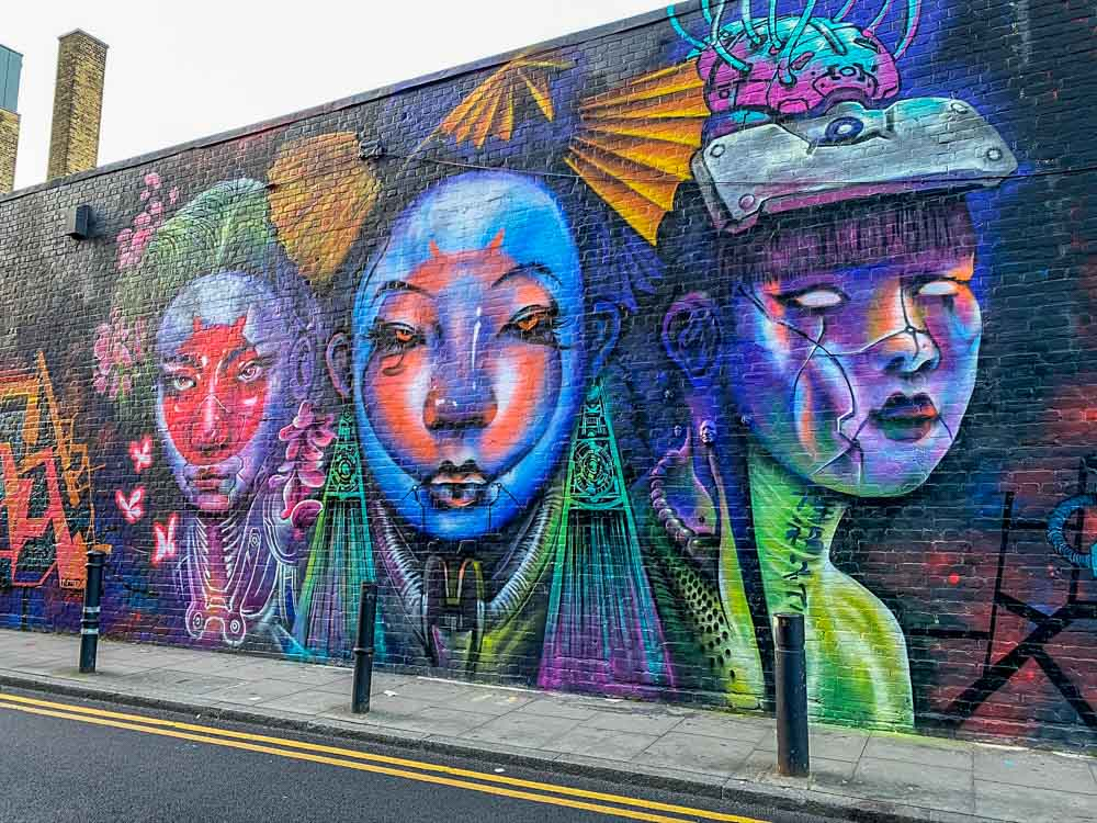Shoreditch Brick Lane Mural on Hanbury St. Purple female figures