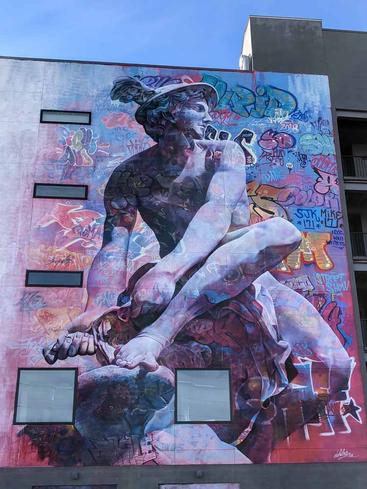 Denver RiNo mural by Pichiavo with man figure and graffiti in blue and purple