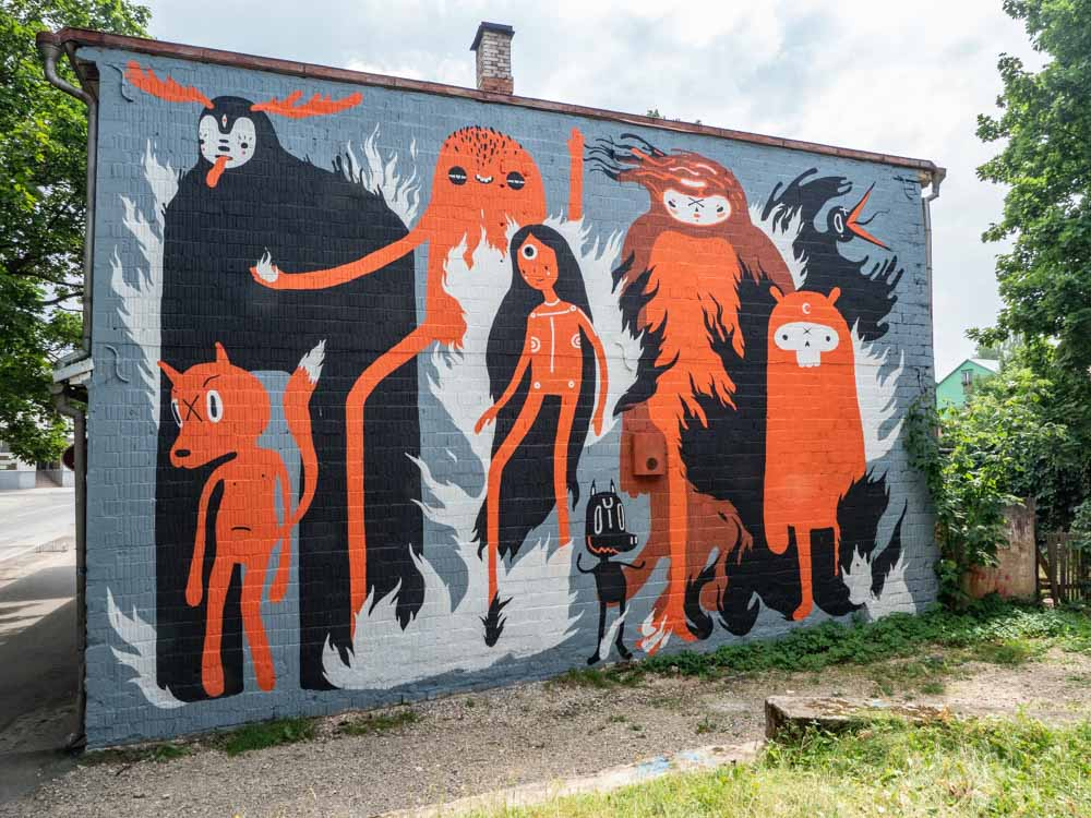 Tartu street art mural by KZRTE. black and orange folk characters