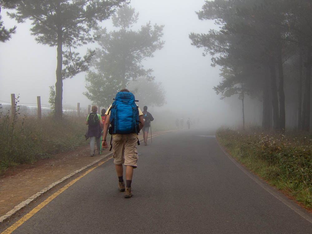 Camino de Santiago hiker with blue backpack and fog