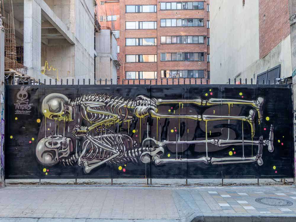 Bogota street art skeleton mural by Nychos. two horizontal skeletons in black and yellow