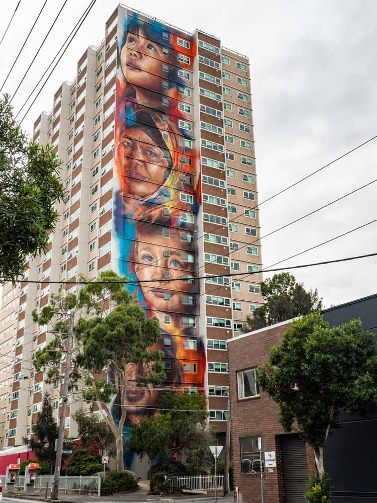 Melbourne mural by Adnate in Collingwood. Portraits of immigrants in blue and orange.