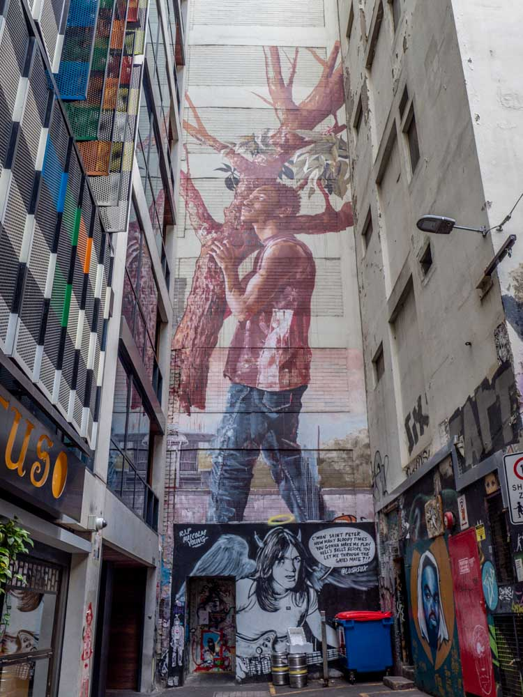 Fintan Magee mural ACDC graffiti lane Melbourne - mural of man carrying a tree