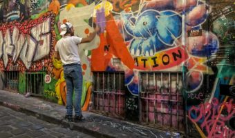 Graffiti Melbourne: Hosier Lane - man spray painting orange paint onto a wall