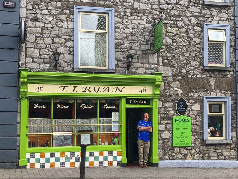 TJ Ryan's Pub in Cashel Ireland. Man in front of green doorway with rock wall