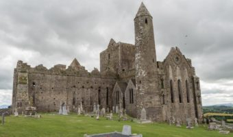 Ireland by Car: Rock of Cashel. Stone castle ruin with gravestones