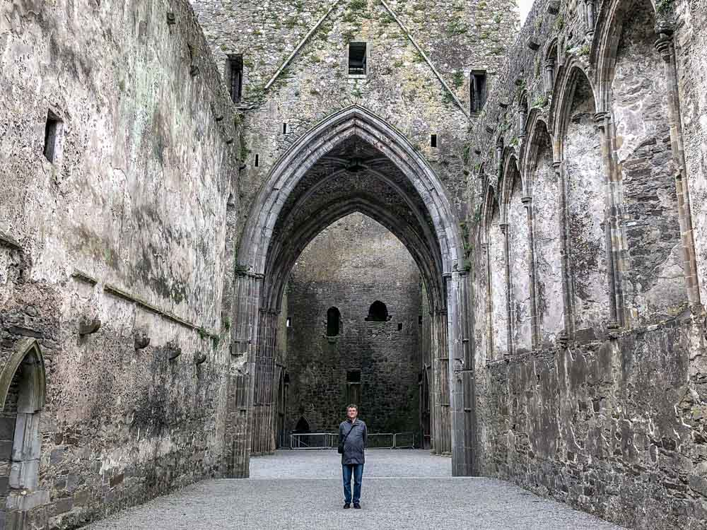 Ireland: Rock of Cashel interior. Man standing in cathedral ruin