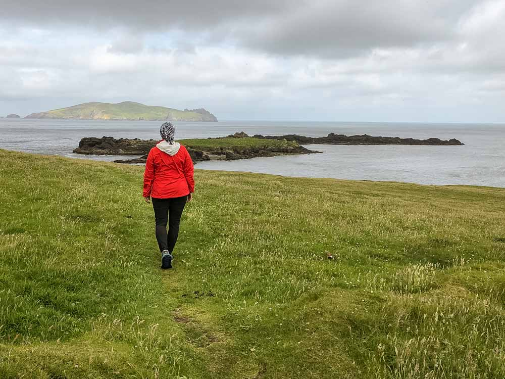 Ireland trip: Great Blasket Island Dingle. Woman in red hiking a cliff