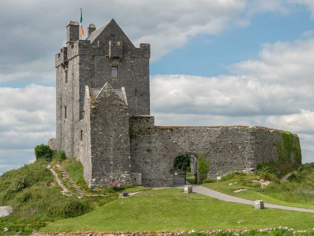 Ireland road trip: Dunguire castle Galway Bay. Castle with green grass and clouds