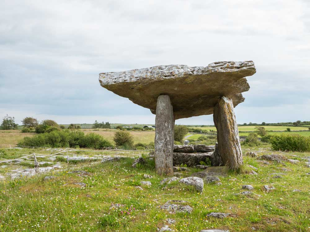 Ireland itinerary the Burren Poulnabrone Dolmen. Burial stones on green landscape