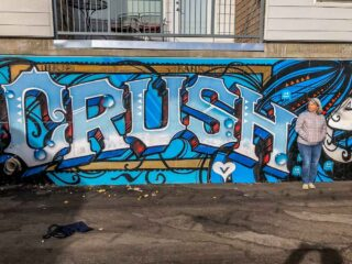 Denver Crush street art festival mural. Blue paint with woman on city street