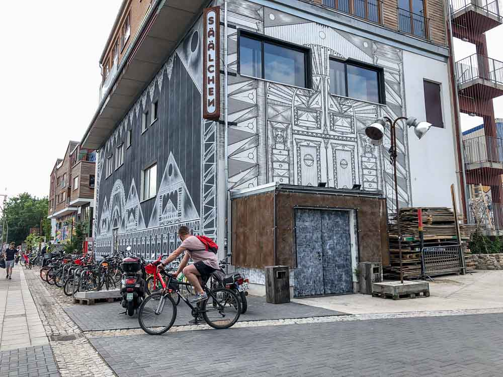 Berlin murals near Holzmarkt. man on bicycle and black and white mural.