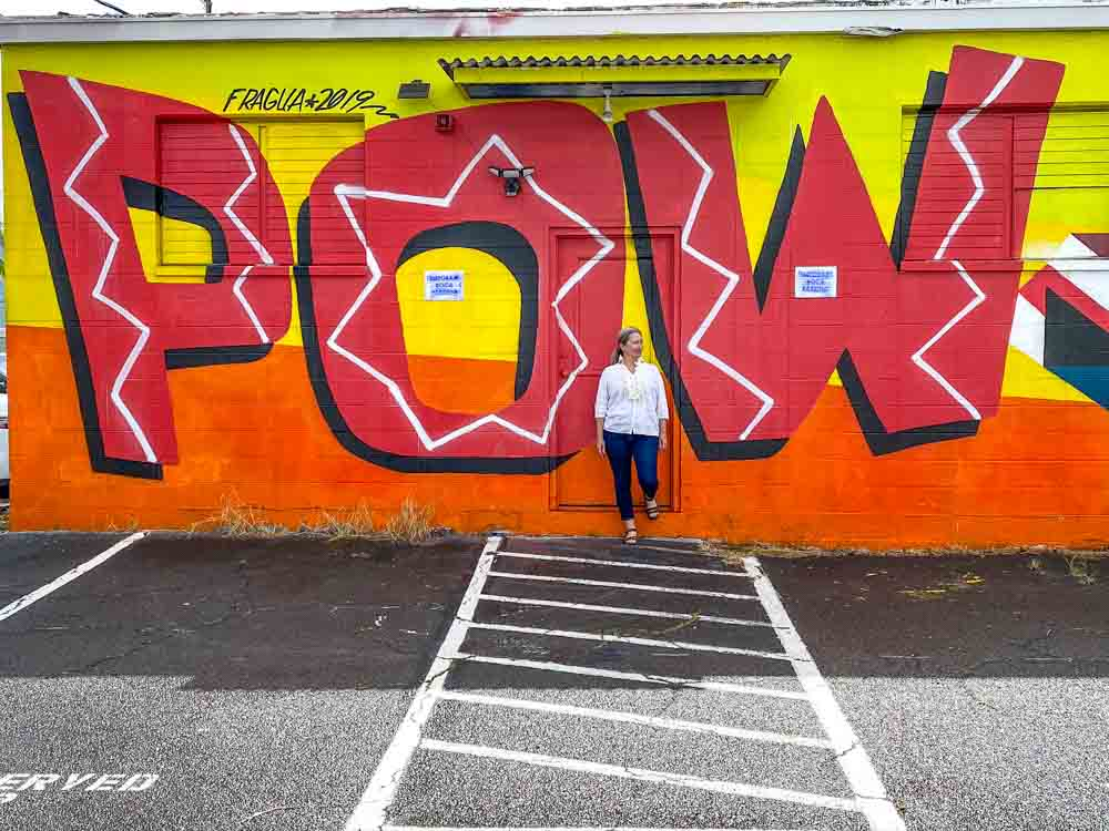 POW!WOW! Hawaii street art mural. Woman standing against a red and yellow mural