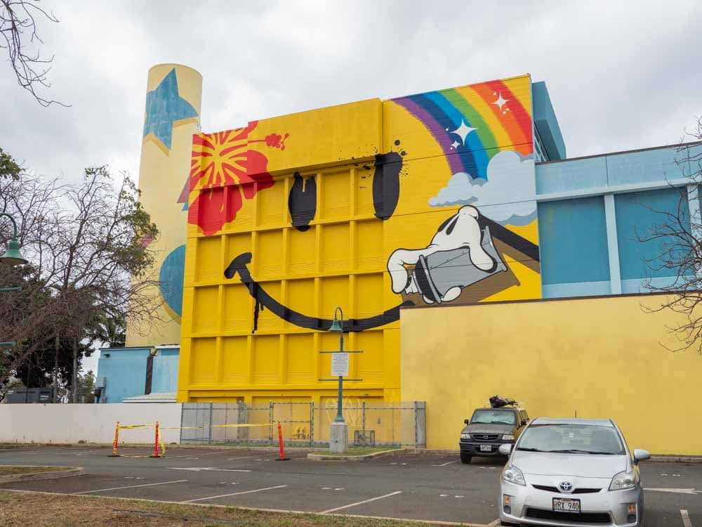 Kakaako street art mural by OG Slick- happy face. Yellow happy face and rainbow on a wall