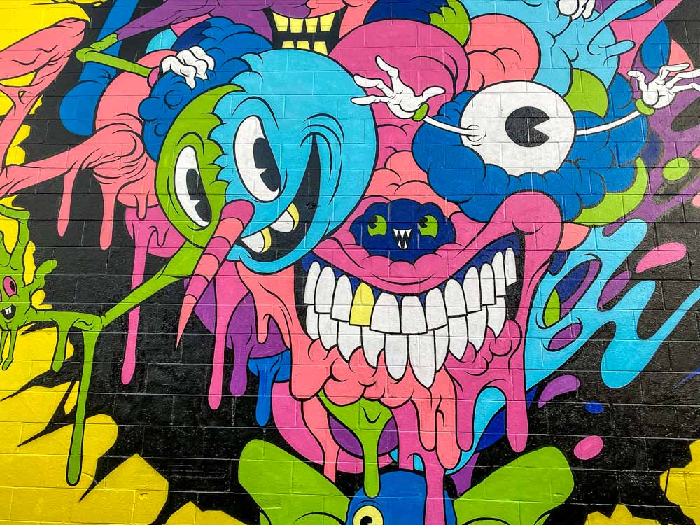 Alex Pardee monster mural on Lana Lane Honolulu. Pink and blue smiling creatures
