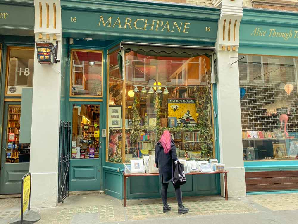 London Bookshops: Cecil Court Marchpane books. Woman with pink hair and green shopfront